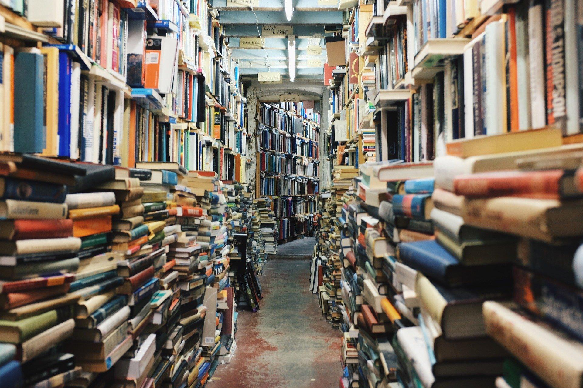 Gang in einem Buchladen: Die Bücher stapeln sich chaotisch bis zur Decke